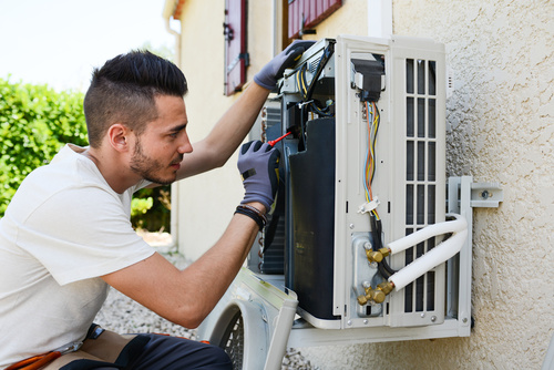 handsome young man electrician installing air conditioning in a